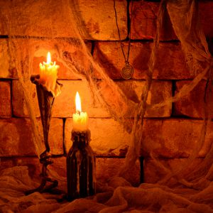 Halloween still life with two burning candles on brick wall